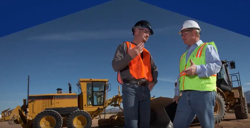 2 men with heavy equipment